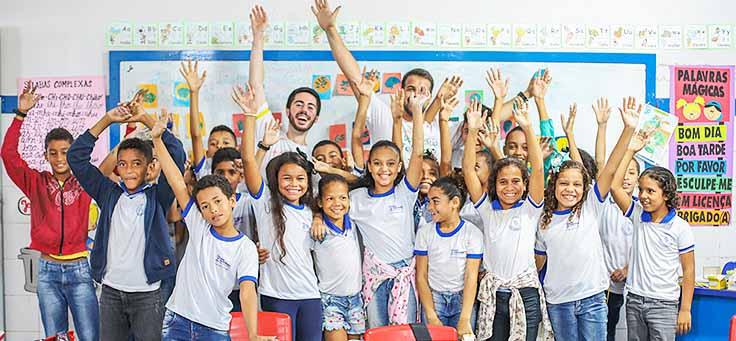 Alunos da Escola Municipal de Ensino Fundamental Frei Fernando estão com braços levantados, posando ao lado de dois participante do programa de voluntariado do Vacaciones Solidárias.