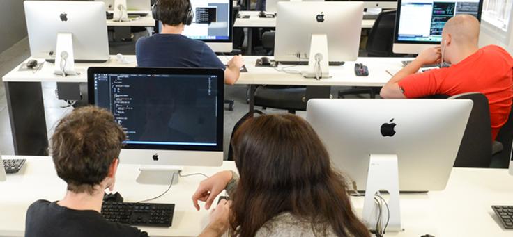 Imagem mostra pessoas trabalhando de costas em seus computadores