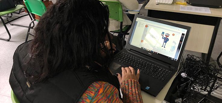 Imagem mostra uma mulher de costas mexendo em um notebook