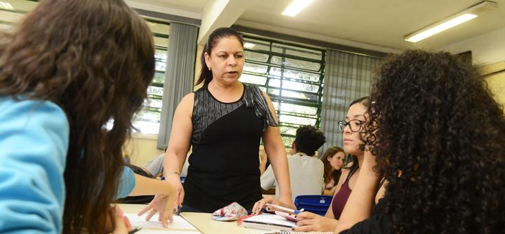 Formadora do Pense Grande, que aplica conceitos de empreendedorismo social em sala de aula, está em pé, ao lado de mesa com grupo de três jovens que ouve atentamente.