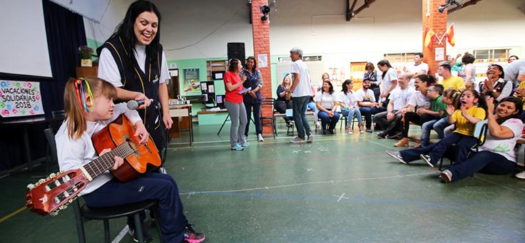 Na imagem, estudantes está tocando violão com auxílio de voluntária em escola de Curitiba. O voluntariado em escolas é uma opção para aproximar a comunidade do ambiente escolar.
