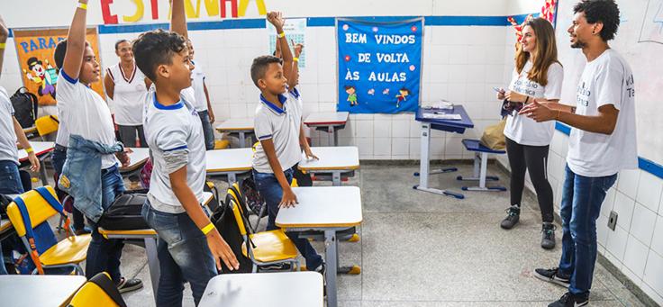 Na imagem, estudantes estão em pé e com as mãos levantadas em sala de aula. Voluntariado em escolas é uma opção para aproximar a comunidade do ambiente escolar.