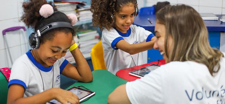 Voluntariado em escolas é uma opção para aproximar a comunidade do ambiente escolar. Na imagem, voluntária interage com estudante que está navegando em tablet e usando fones de ouvido.