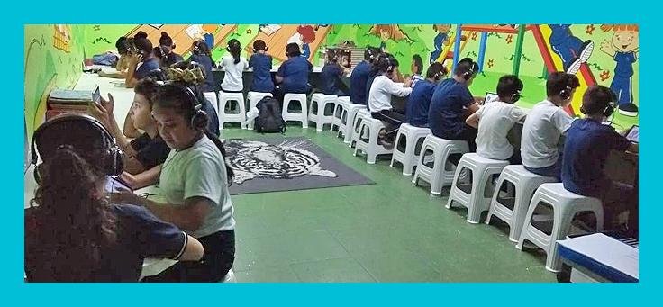 Alunos estão sentados lado a lado, usando tablet e fones de ouvido, em meio a Sala Parque, um dos projetos incentivados pelo Aula Digital, da Fundação Telefônica Vivo. A Sala Parque tem as paredes pintadas em cores vivas, com desenhos de crianças brincando em um parquinho.