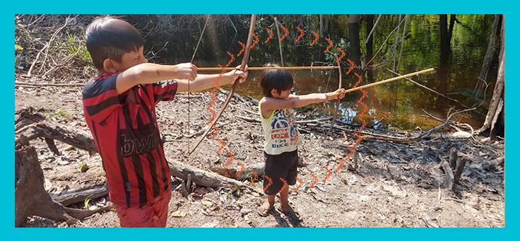 Imagem mostra duas crianças manuseando um arco e flecha