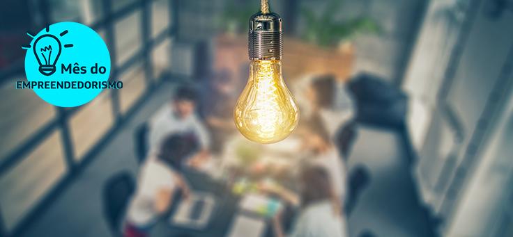 Imagem mostra uma lâmpada acesa sobre pessoas sentadas ao redor de uma sala de reunião para representar 10 empreendedores sociais que estão mudando o mundo segundo a Fundação Schwab.