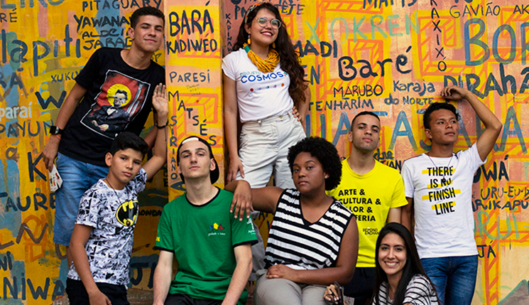 Oito jovens que participaram do jogo colaborativo Primavera X posam em frente a parede grafitada. Um deles é Rhenan Cauê, que está usando a camiseta do personagem Batman e organizou uma Liga na cidade de Araguatins (TO).