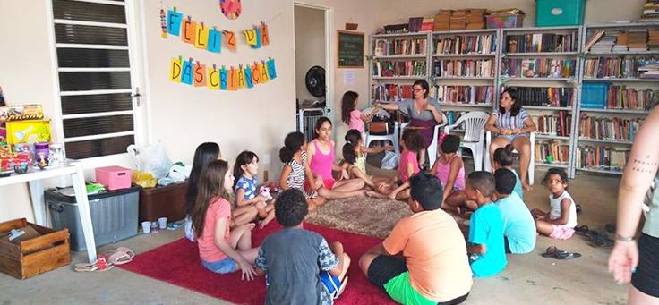Imagem mostra crianças sentadas em uma roda no chão, na garagem adaptada para a biblioteca comunitária criada pelo Coletivo Literocupa