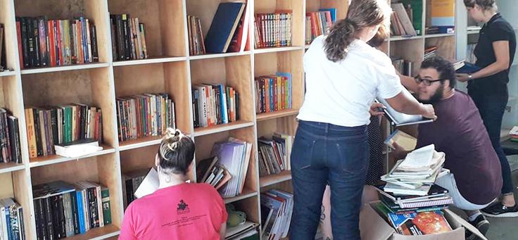 Imagem mostra pessoas arrumando livros na estante do espaço da bbiblioteca comunitária Mundo da Lua