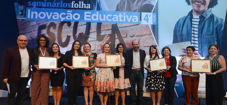 Ganhadores da votação popular posam para foto no palco, ao lado do apresentador Marcelo Tas