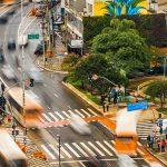 Na imagem ônibus e carros aparecem desfocados em ruas de São Paulo para ilustrar iniciativas voluntárias que transformam a vida na cidade.
