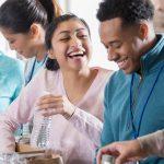 Imagem mostra grupo de pessoas sorrindo enquanto tiram mantimentos da caixa de papelão