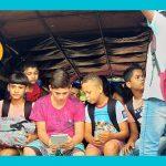Imagem mostra um grupo de crianças sentadas em um caminhão pau de arara