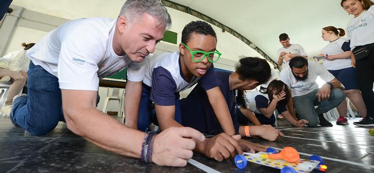 Voluntário e jovem brincam com carrinho feito de materiais recicláveis no CENHA, onde voluntários do Vacaciones Solidárias ensinaram programação para pessoas com deficiência intelectual.