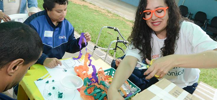 Voluntária ajuda jovem a colar adereços em robô no CENHA, onde voluntários do Vacaciones Solidárias ensinaram programação para pessoas com deficiência intelectual.