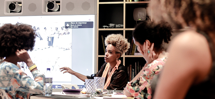 A imagem mostra quatro mulheres dentro de uma sala. Sentadas em volta de uma mesa, três delas olham para frente, onde se vê uma imagem em projeção, apresentada por outra mulher.