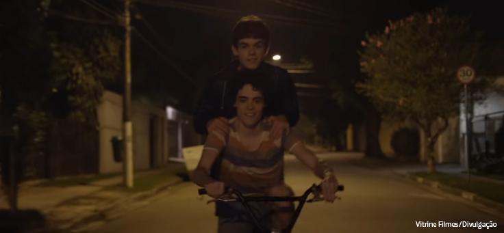Menino está guiando bicicleta com amigo apoiado no ombro dele em cena de Hoje Eu Quero Voltar Sozinho, que está em lista de filmes que debatem direitos humanos.