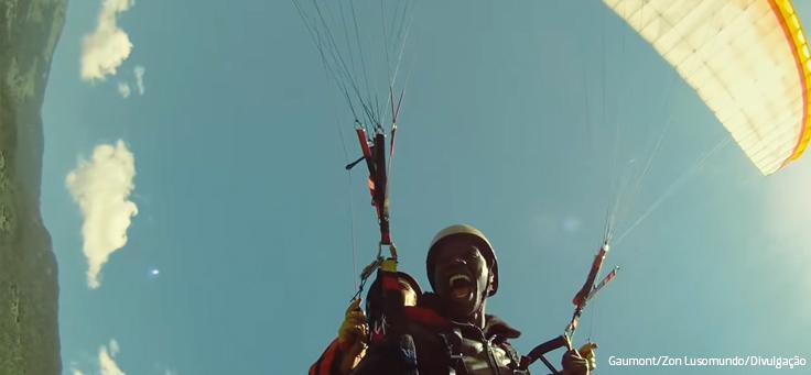 Dois homens estão sorrindo e pulando de paraquedas em cena de Os Intocáveis, que está em lista de filmes que debatem direitos humanos.