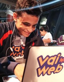 Imagem mostra jovem usando um notebook que leva o adesivo da iniciativa Vai na Web