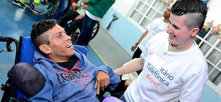 Imagem mostra voluntária conversando com pessoa com deficiência.