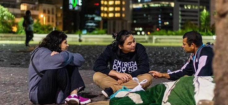 Imagem mostra três pessoas sentadas conversando.