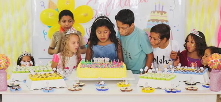 Crianças comemoram aniversário atrás da mesa, decorada com doces e bolo.