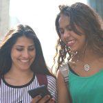 Imagem mostra duas jovens sorrindo enquanto olham para um celular