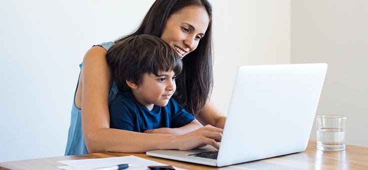 Imagem mostra mãe e filho olhando para um notebook