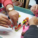 Imagem mostra pessoas manuseando bonecas, peças de lego e utensílios de madeira