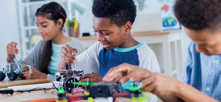 Imagem mostra três estudantes fazendo atividades maker