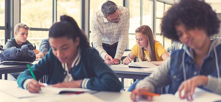 Imagem mostra estudantes em sala de aula. Um professor se inclina para tirar dúvidas.