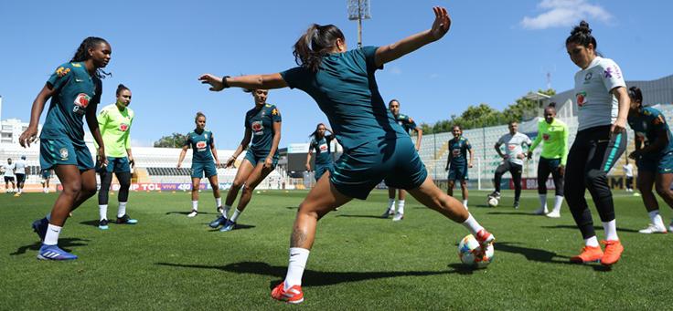 Mulheres formam roda em atividade com bola em campo de futebol no Programa de Oportunidades e Direitos, que contribui para formação de jovens.