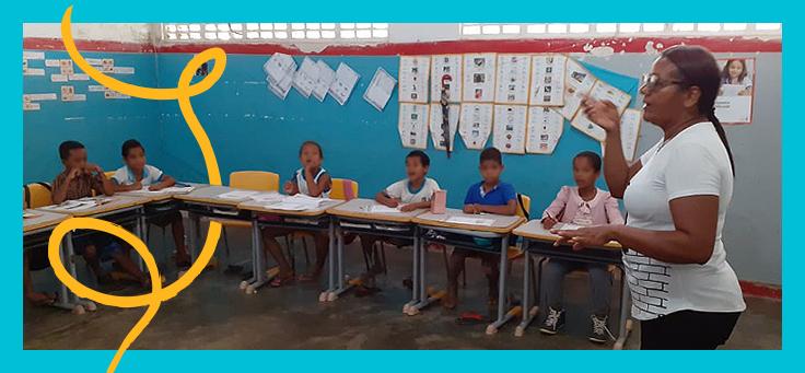 Educadora Marleide dos Santos Vasconcelas está em meio a carteiras de estudantes em sala de escola apoiada pelo projeto Aula Digital.