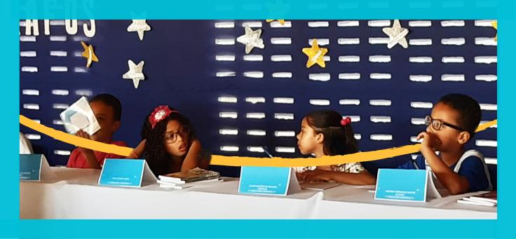 Imagem mostra grupo de quatro estudantes sentados em frente à mesa de autógrafos. Os nomes deles estão sobre a mesa. Ao fundo se veem algumas estrelas douradas e prateadas usadas como decoração.