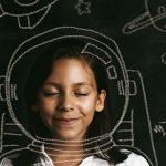 Imagem mostra menina de olhos fechados. Atrás dela há uma lousa com elementos que remetem ao espaço desenhados com giz: foguetes, planetas. Um capacete de astronauta dá a impressão de estar na cabeça da criança.