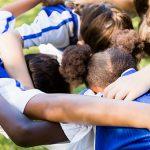 Imagem mostra um grupo de pessoas abraçadas olhando para baixo em um gramado