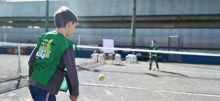 Imagem mostra duas crianças jogando tênis em uma quadra
