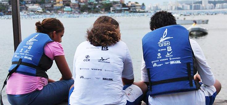 Imagem mostra três pessoas de costas olhando para o mar