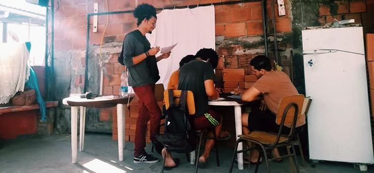 Jovem com cabelos crespos presos em rabo de cavalo orienta outras três jovens sentados em carteiras no projeto Unifavela, que contribui para a formação de jovens.