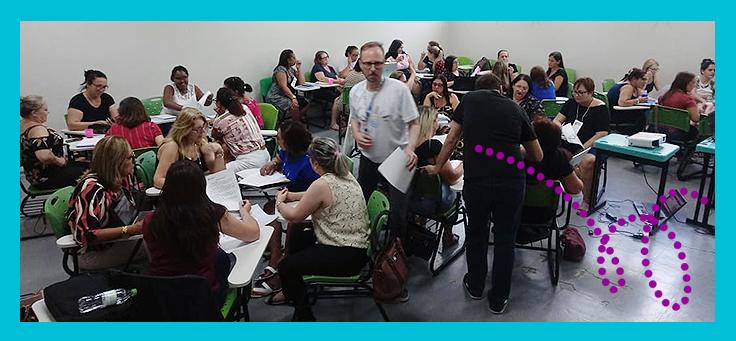 Imagem mostra diversos professores sentados, dentro de uma sala de aula, reunidos em grupos