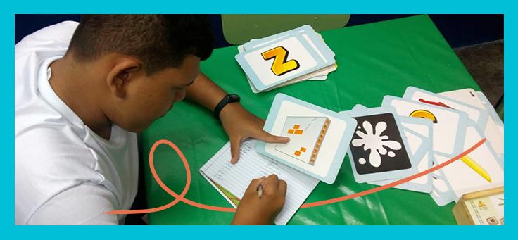 Imagem mostra um jovem escrevendo em um caderno enquanto segura um cartão com um desenho na outra mão