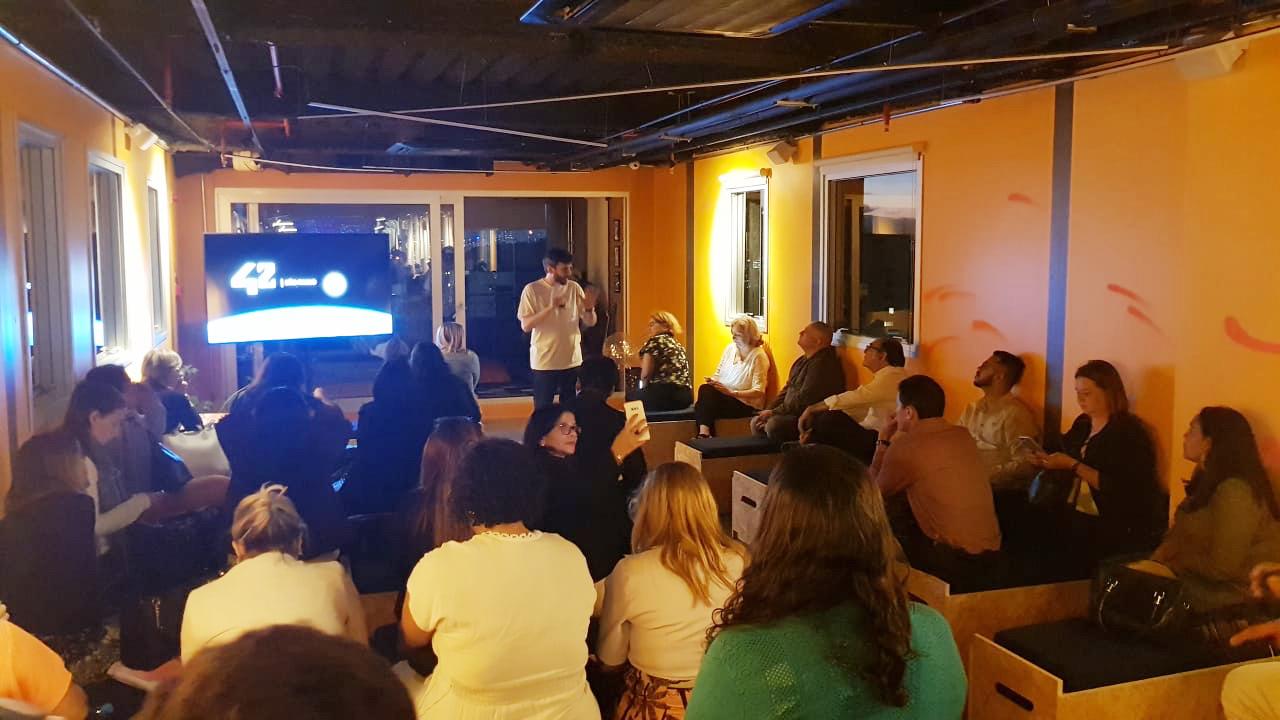 Técnicos de secretarias de educação estão sentados em fileiras em auditório na sede da 42 São Paulo para debater inovação e novo ensino médio.