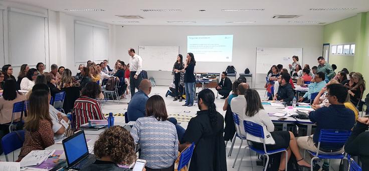 Imagem mostra técnicos de secretarias de ensino de diversos Estados reunidos em grupos em uma sala de aula durante evento do Consed para discussão do novo ensino médio.