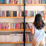 Mulher está de costas para estante com cinco nichos cheios de livros, que ilustram pauta sobre obras essenciais para formação de professores.