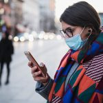 Imagem mostra uma mulher na rua usando uma máscara cirúrgica e vestindo casaco e cachecol. Ela está olhando para a tela de um celular que está em suas mãos.