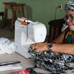 Mulher negra usando turbante e óculos está costurando peças em uma máquina para ilustrar negócios inseridos na economia solidária.