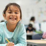 Imagem mostra menina de camiseta verde em primeiro plano segurando um lápis numa sala de aula. Atrás dela é possível ver outros estudantes.