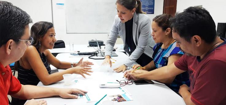 Imagem mostra um grupo de educadores reunidos em uma sala em volta de uma mesa