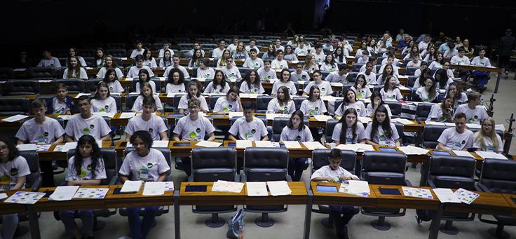 Imagem mostra grupo de crianças do projeto Câmara Mirim sentados em uma plenária