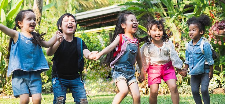 Imagem mostra um grupo de crianças de mãos dadas sorrindo ao ar livre com uma vegetação ao fundo